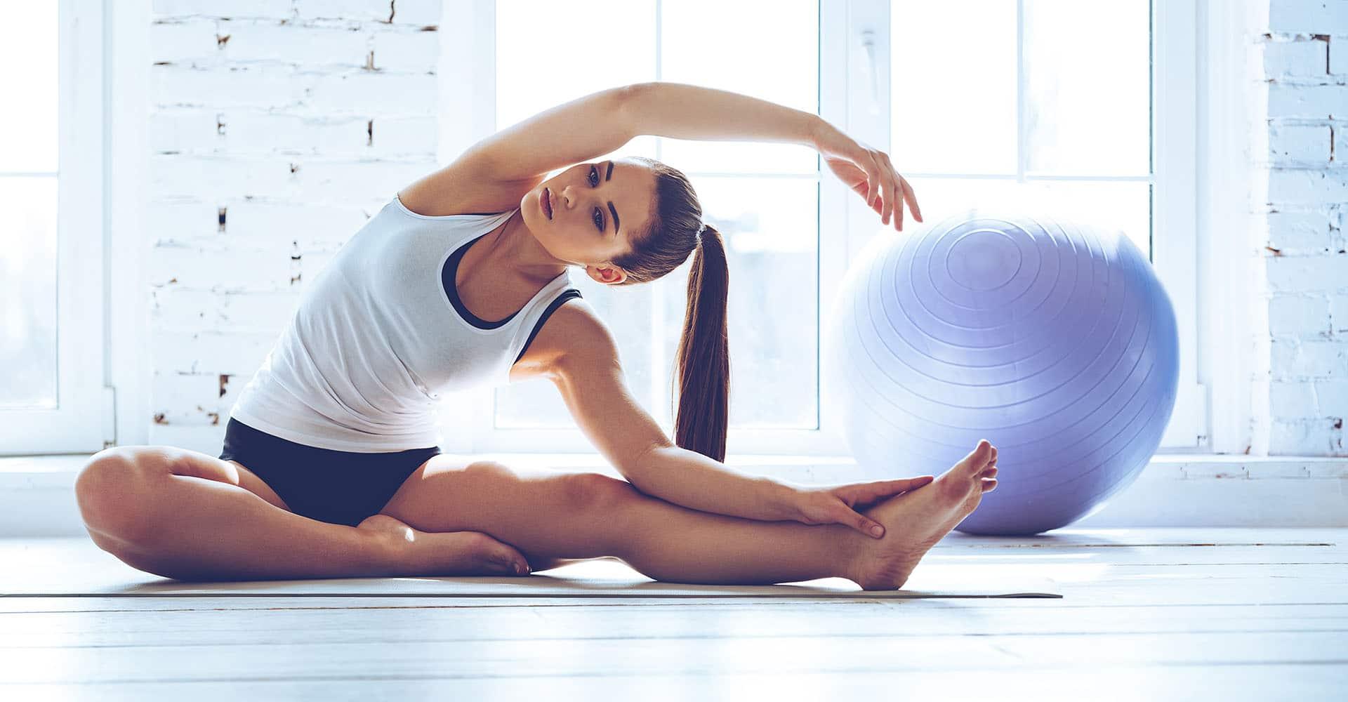 Frau trainiert zuhause mit Gymnastikball