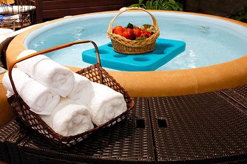 Korb mit Tüchern auf Whirlpool-Umrandung aus Rattan