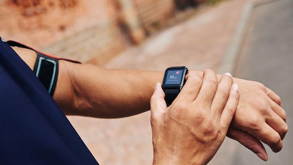 Mann kontrolliert Puls an Smartwatch