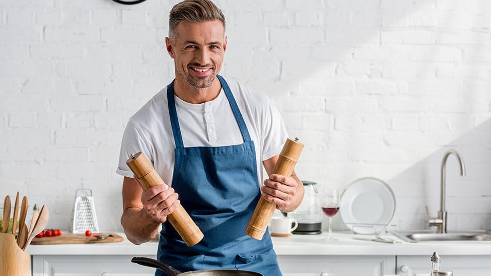 Mann mit 2 Pfeffermühlen in Händen