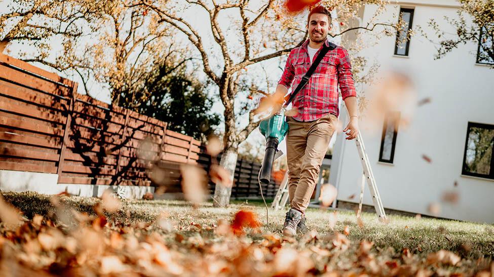 Mann mit Laubsauger in Garten