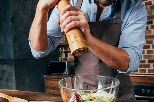 Mann nutzt Pfeffermühle in Küche