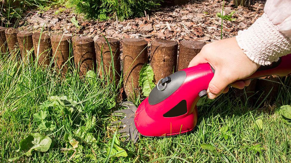 Mann schneidet Rasen mit Akku-Grasschere