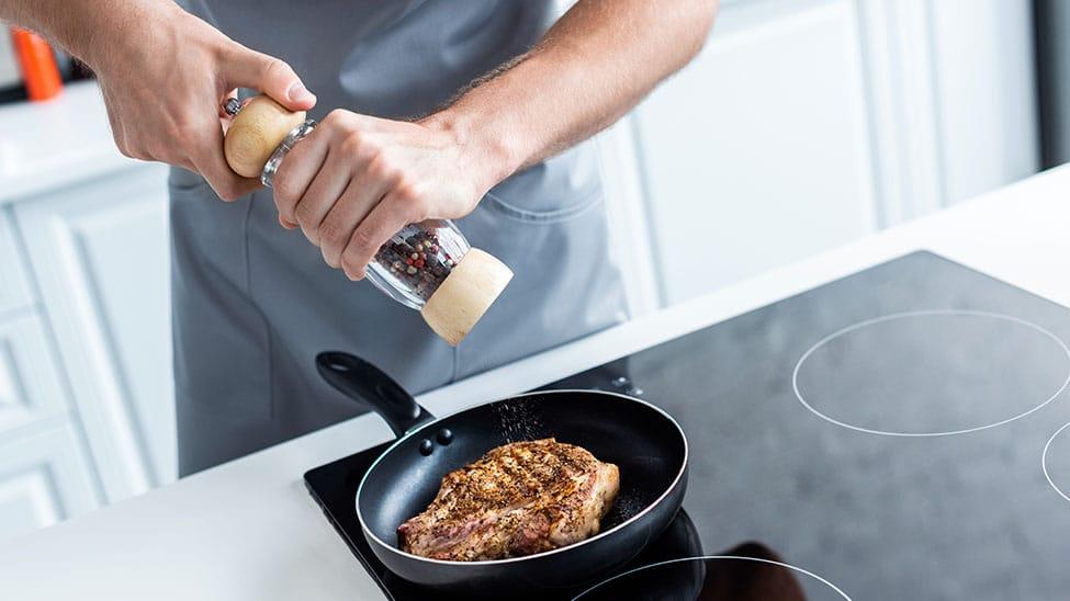 Mann würzt Steak mit Pfeffermühle