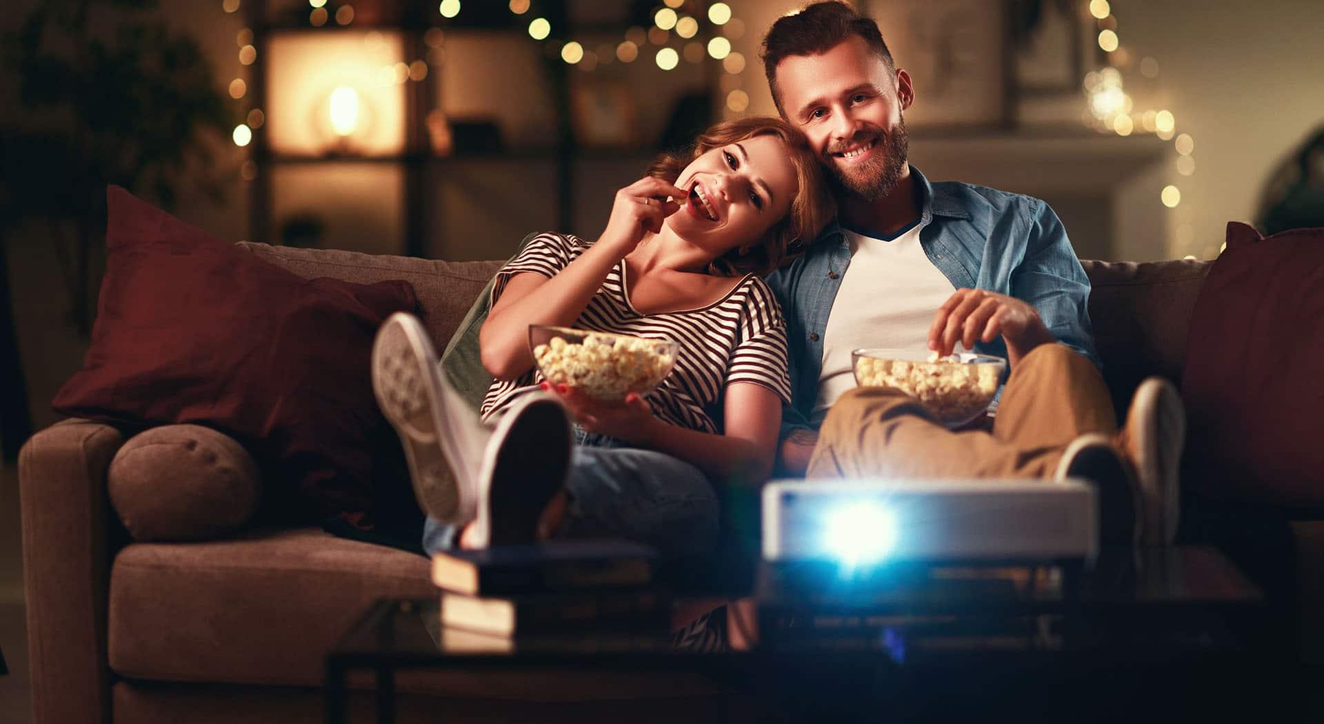Paar schaut im Wohnzimmer Film mit Mini Beamer