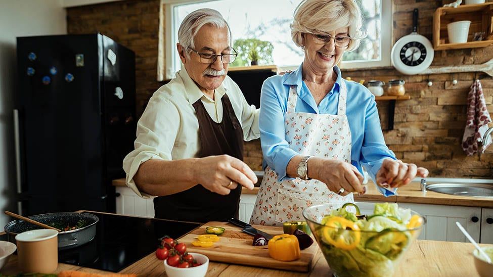 Senioren-Paar bereitet cholesterinarme Nahrung zu