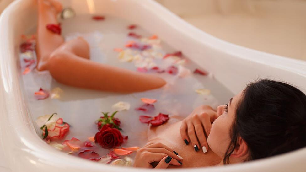 Frau badet in Rosenwasser und Rosen