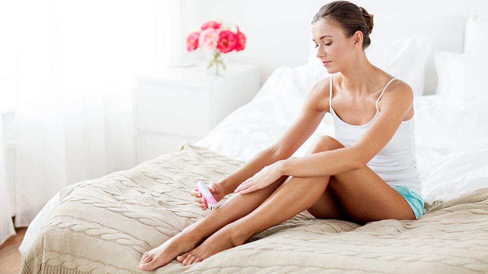 Frau bearbeitet Beine mit Epilierer
