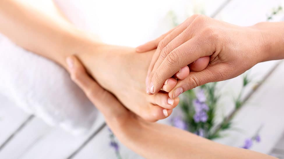 Frau kriegt am Fuß Behandlung gegen Nagelpilz