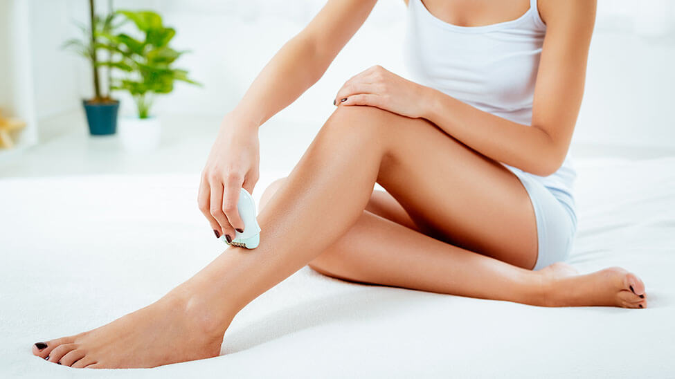 Frau nutzt Epilierer für ihre Beine