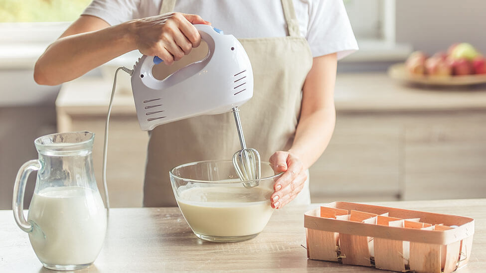 Frau nutzt Handmixer in Küche