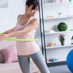 Frau trainiert zuhause mit Hula Hoop Reifen