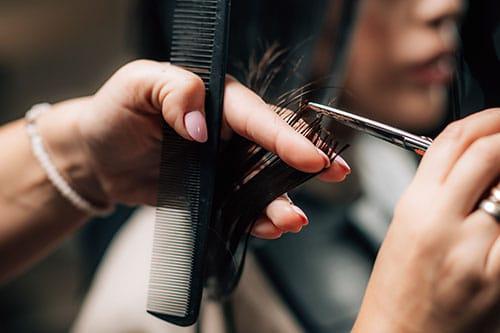 Frau werden mit Friseurschere Haare geschnitten