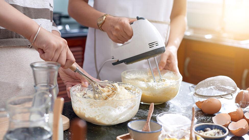Freundinnen kochen mit Handmixer in Küche