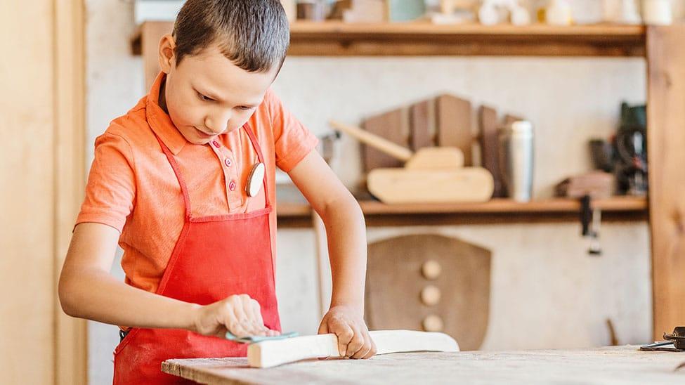 Junge schleift an Werkbank für Kinder