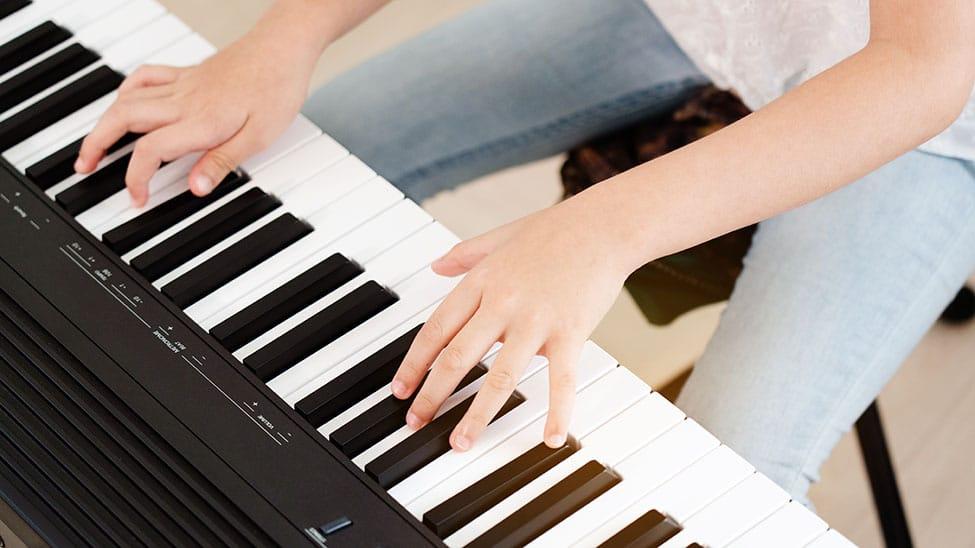 Junge spielt E Piano