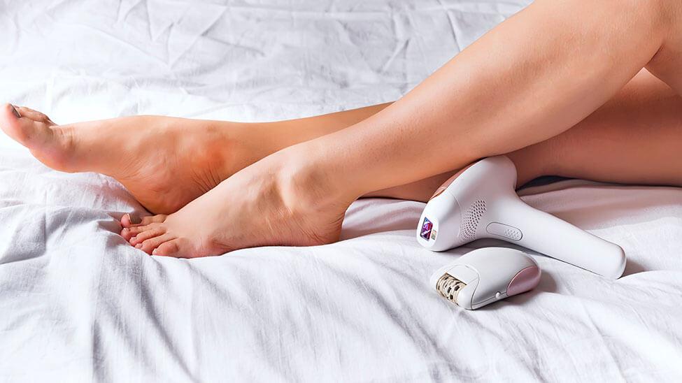 Laser Epilierer neben Frau auf Bett