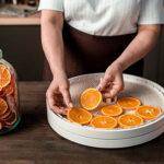 Mann legt Orangen in Dörrautomat