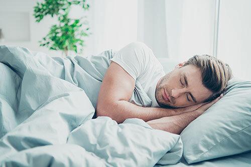 Mann schläft auf Matratze für Seitenschläfer