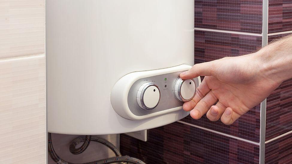 Mann stellt Temperatur an Durchlauferhitzer in Küche ein