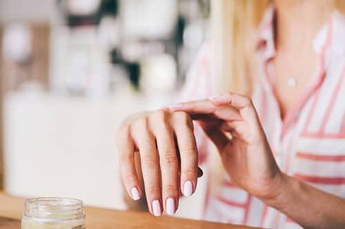 Frau trägt Handcreme auf Hand auf