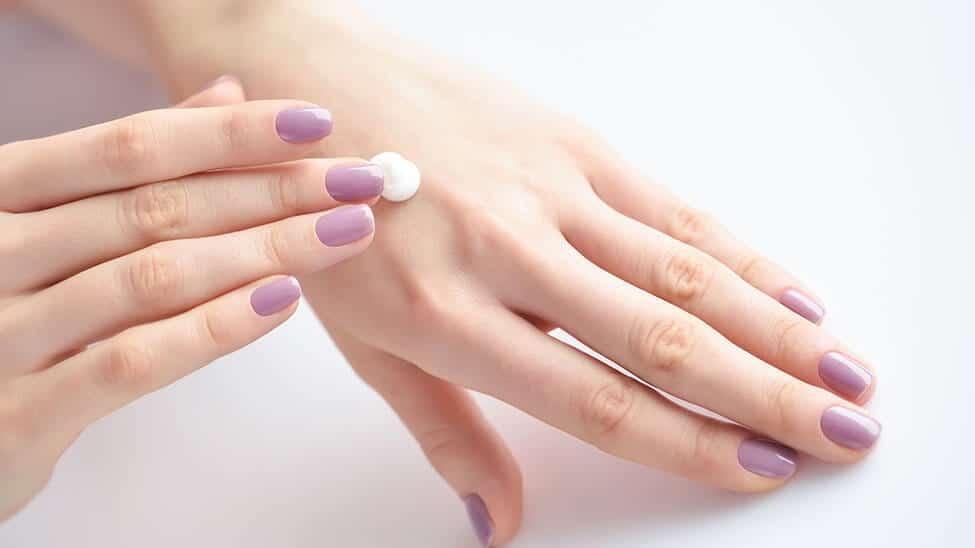 Frau trägt Handcreme auf gepflegte Hände auf