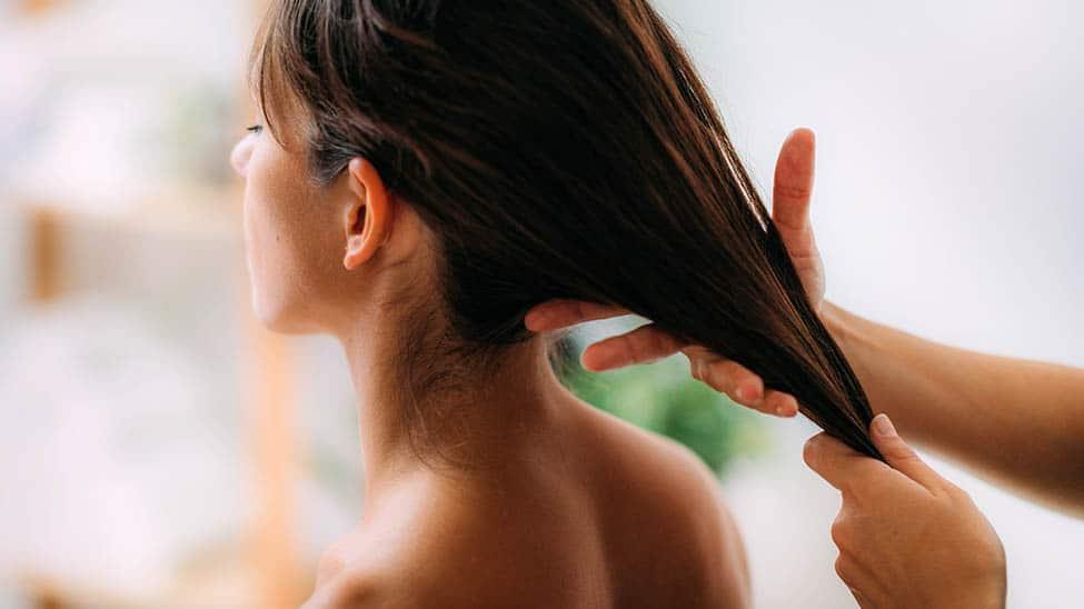 Frau bekommt in Haaren Behandlung mit Rizinusöl