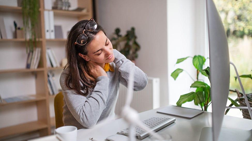 Frau hat Nackenschmerzen im Home Office