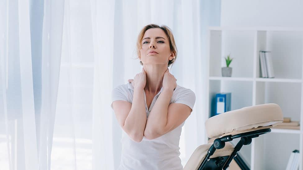 Frau hat Nackenschmerzen vor Nutzung eines Nackenmassagegerät