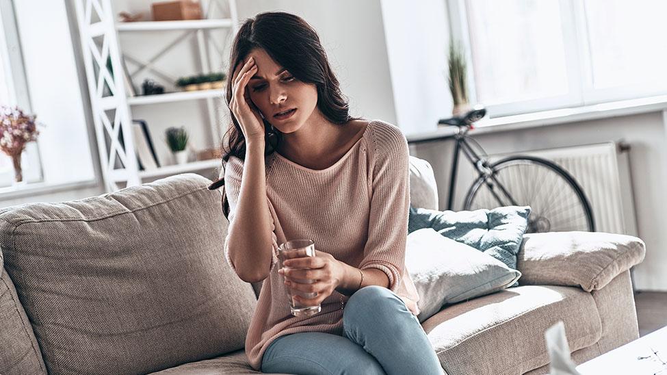 Frau leidet unter Verspannungen am Kopf und braucht Kopfmassage