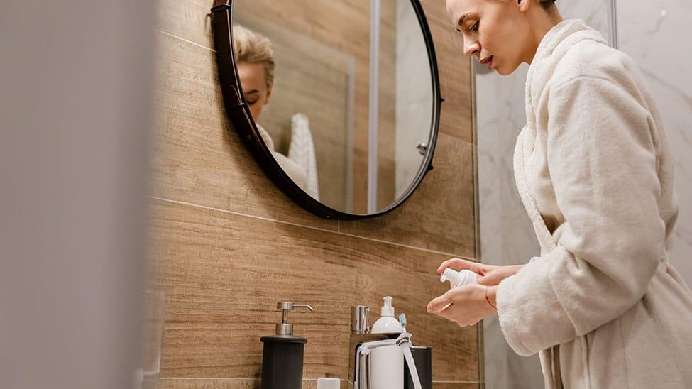 Frau nimmt Bodylotion nach Dusche in Hand