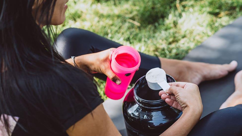 Frau nimmt Eiweißpulver mit Messbecher aus Behälter