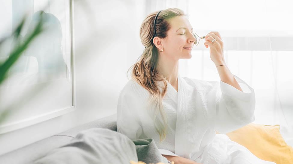 Frau nutzt Nadelroller auf Gesicht