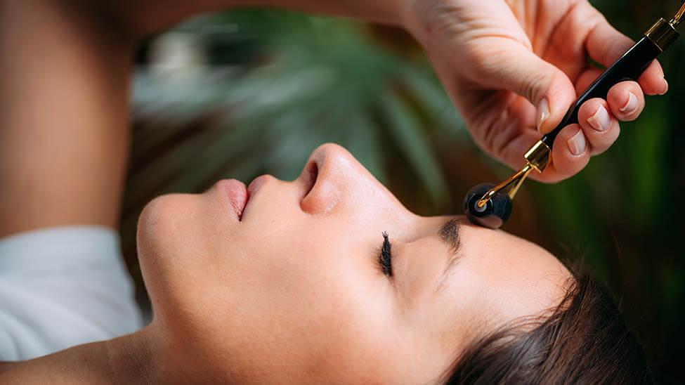 Frau nutzt Nadelroller auf Stirn