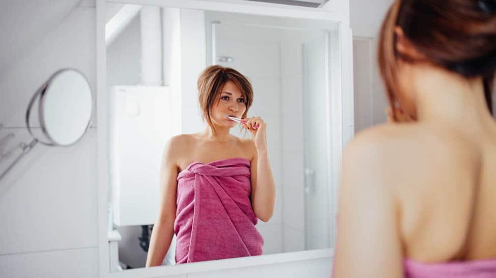 Frau putzt Zähne im Bad