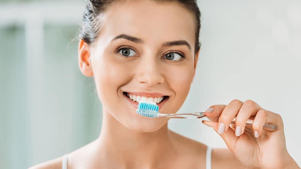 Frau putzt mit blauer Zahnpasta Zähne