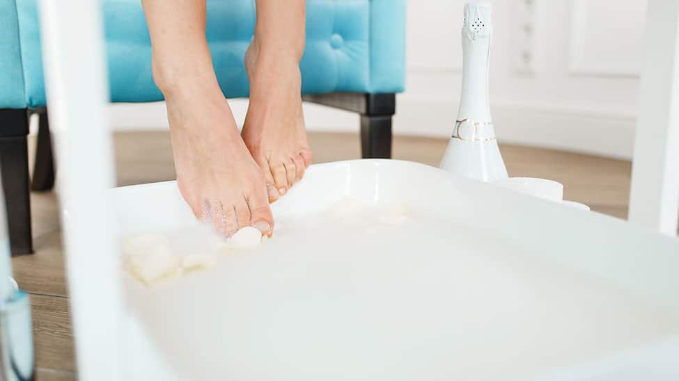 Frau steckt Füße in Fusssprudelbad