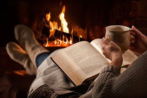 Mann macht Feierabend mit Buch und Tee am Kamin
