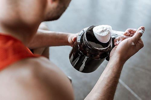 Mann nimmt mit Messbecher Workout Booster