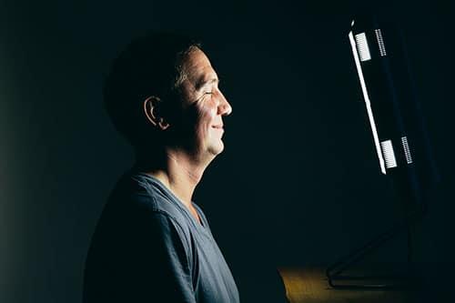 Mann nutzt Lichttherapie Lampe zuhause