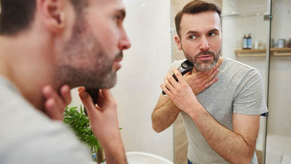 Mann rasiert sich mit Rasierapparat Gesicht