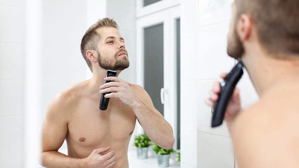 Mann rasiert sich mit Rasierapparat vor Spiegel