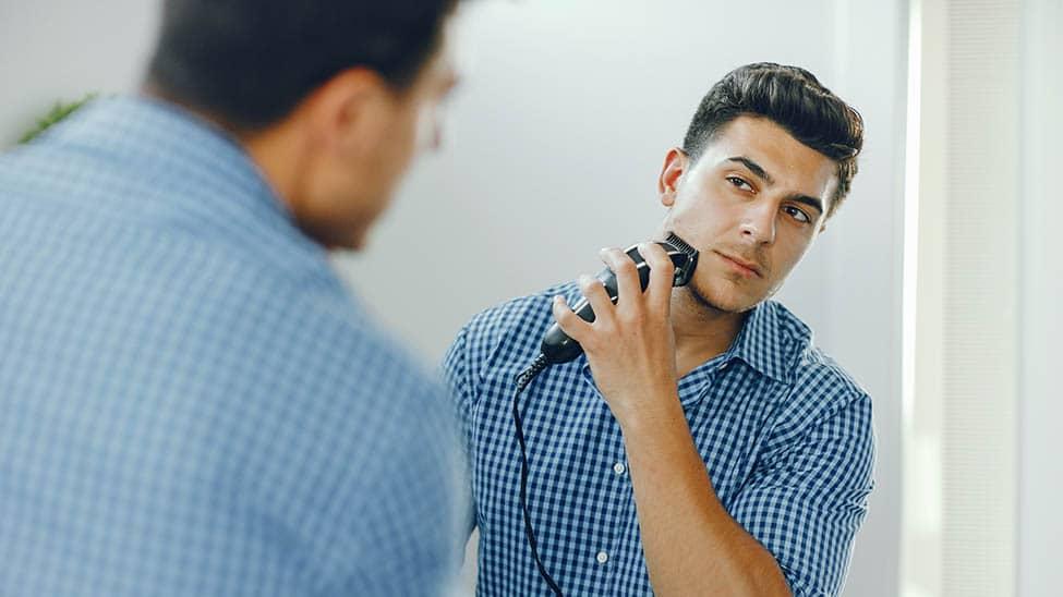 Mann rasiert sich mit elektrischem Rasierapparat