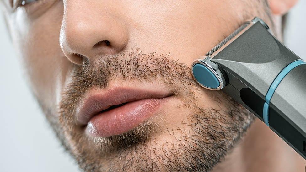 Mann rasiert sich mit elektrischem Rasierer