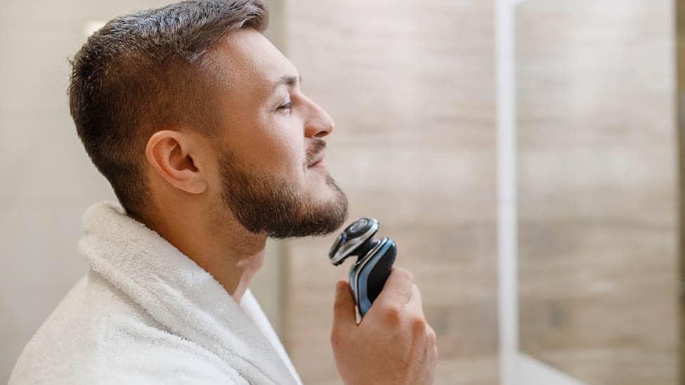 Mann stutzt sich Bart mit Rasierapparat vor Spiegel