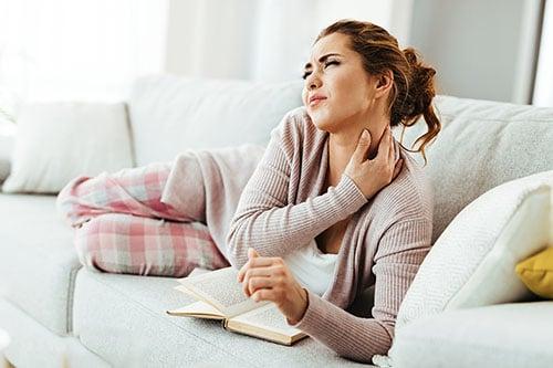 Frau auf Sofa mit Nackenschmerzen