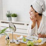 Frau betreibt Gesichtspflege am Spiegel zuhause