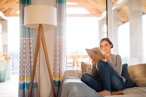 Frau genießt Leben und entspannt bei einem Buch auf Sofa zuhause