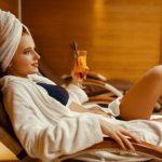 Frau genießt auf Saunaliege Cocktail