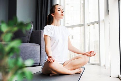 Frau im Schneidersitz auf Meditationsmatte im Wohnzimmer